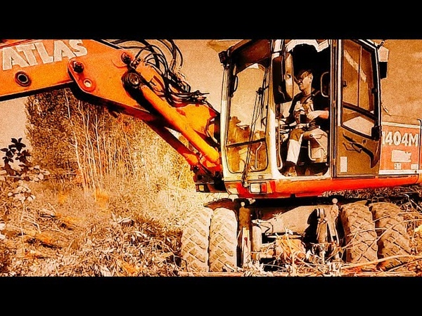 Atlas 1404M Wheel Excavator With Bucket Clamp Clearing A Ditch