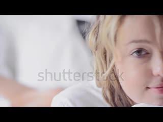 Stock-footage-cute-blond-woman-in-lifestyle-scene-in-white-luxury-bedroom