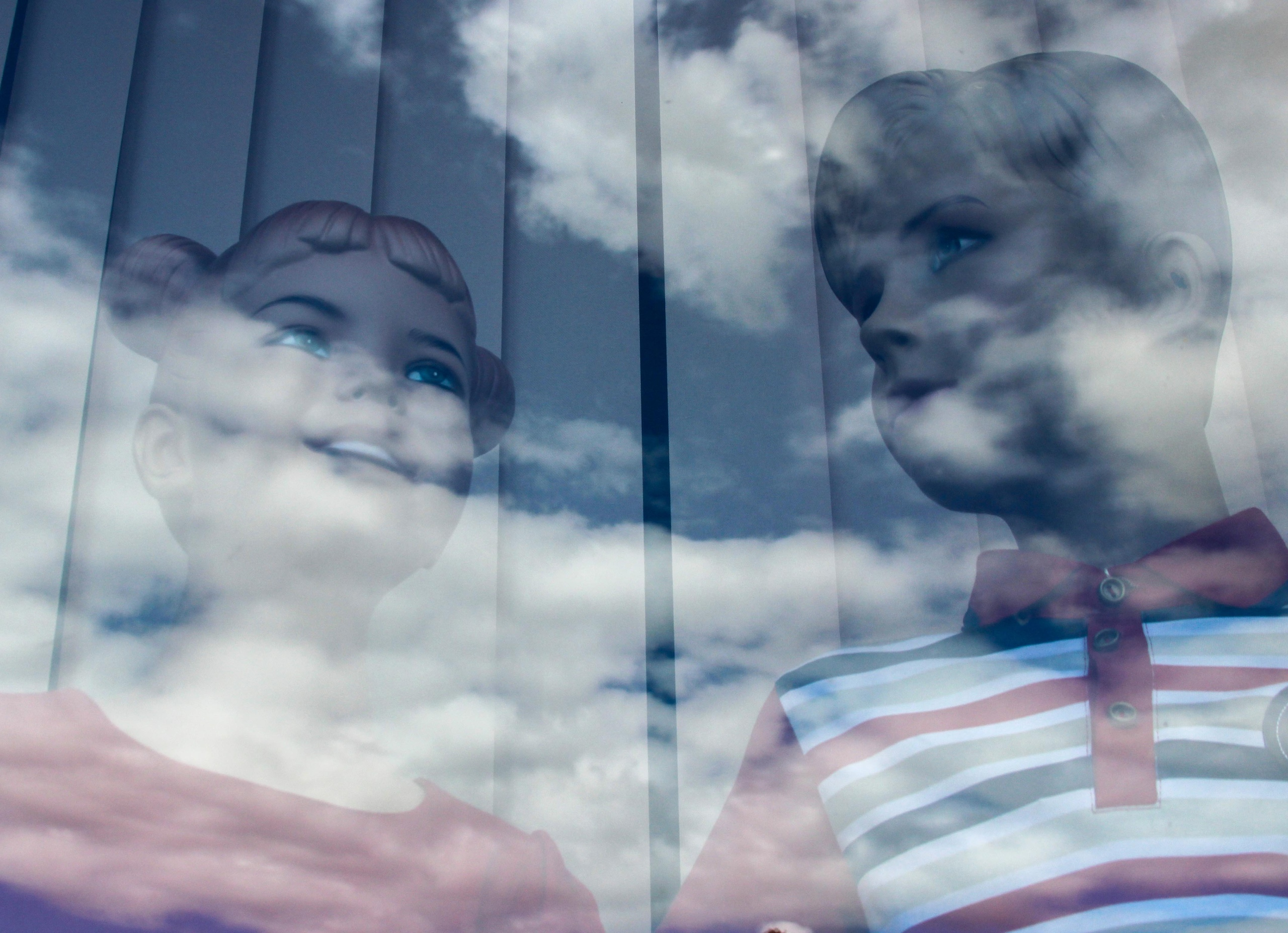 манекены за стеклом в стекле отражается небо