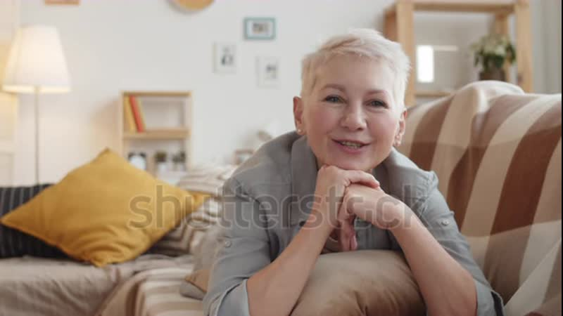 Stock footage chest up shot of lovely smiling mature caucasian woman with short grey hair lying on stomach on