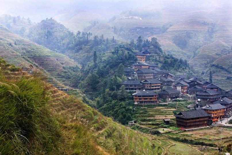 Деревня с традиционными домами у рисовых полей в Лунцзи, провинция Гуанси, Китай. Лукас Шифрес / Getty Images