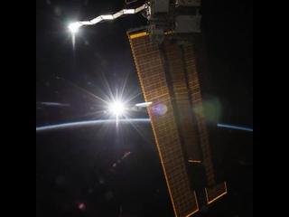 Замедленная съемка Международной космической станции, завершающей облет Земли без захода солнца, когда она движется рядом с лини