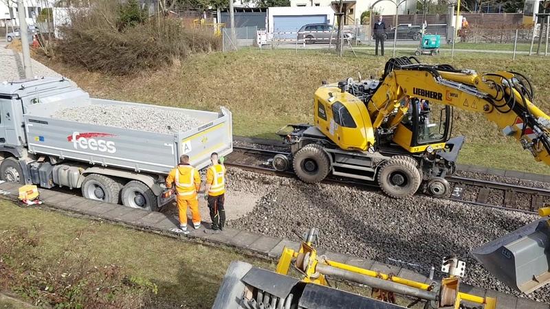 Zweiwegebagger und LKW Schotter aus lehrt